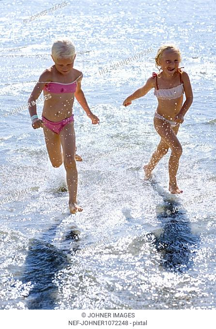 Two girl running in shallow water