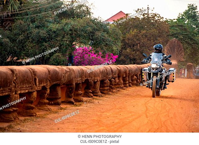 Man riding ADV motorcycle on the Kampong Kdei or dragon bridge in Cambodia