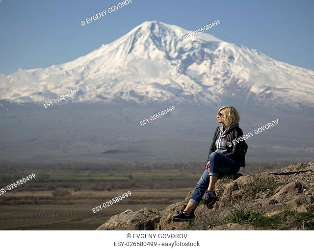 Beautiful blonde woman with curly hair is looking into the distance near of the Ararat Mountain
