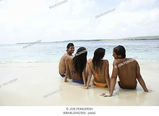 South American couples sitting on beach