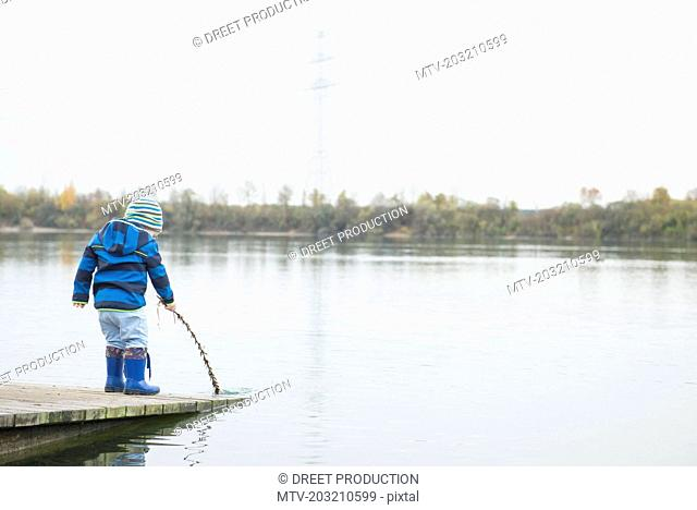 Little boy standing on a landing jetty on lake holding branch into water