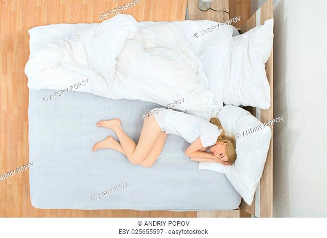 Young Woman Sleeping On White Bed In Bedroom