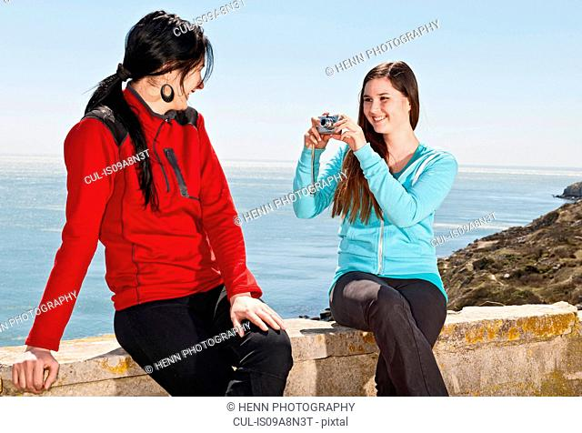 Teenager photographing friend at the coast