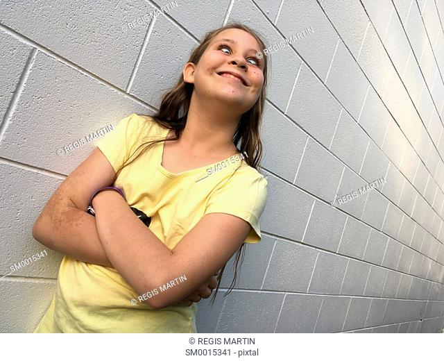 young girl leaning against a white brick wall and looking at the camera while crossing her arms and pulling face