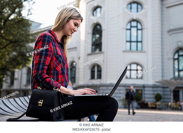 Fashionable young woman sitting on bench outdoors working on laptop