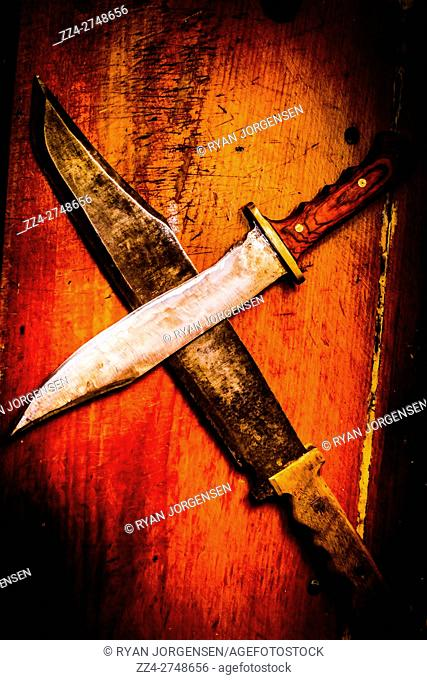 Old warfare still-life photo of battle knives overlapped in cross shape on table. Dueling a challenge of war