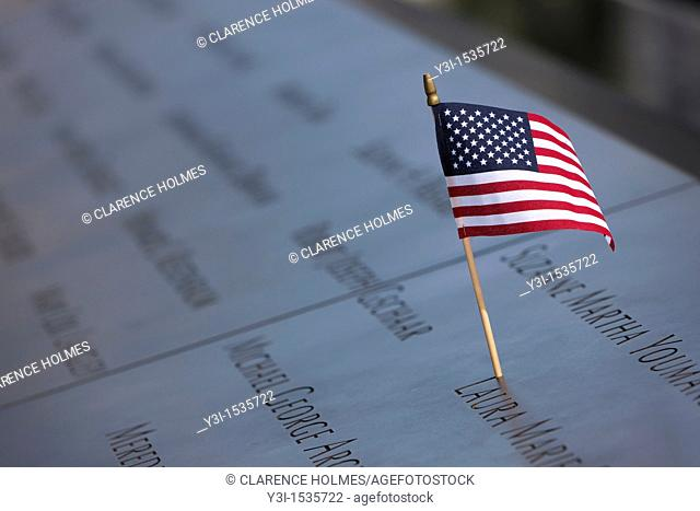A small American flag left on the names inscribed in the perimeter of one of the pools at the National September 11 Memorial in New York City, New York, USA