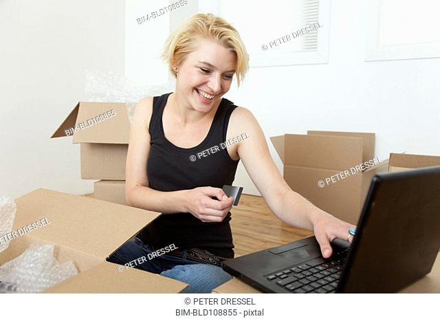 Caucasian woman shopping online in new home