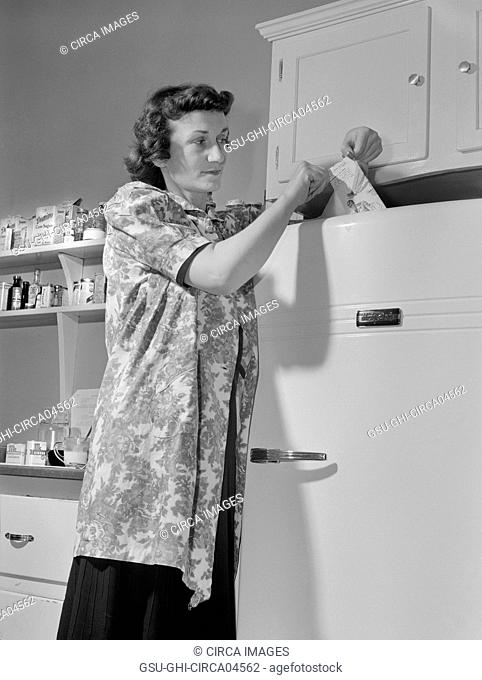 Woman Using Slip of Paper to see if Refrigerator is Wasting Valuable Electric Power and if the Paper can be Pulled out, have the Gasket Tightened or Replaced...