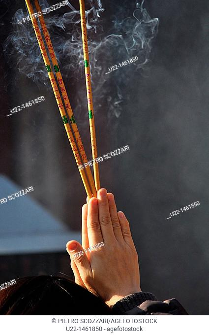 Beijing (China): a person prays burning incense at the Dongyue Temple during the Spring Festival