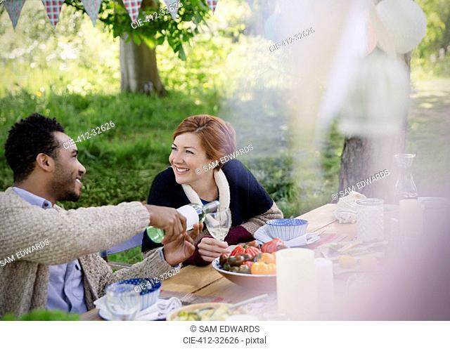 Smiling couple pouring wine at garden party table