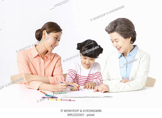 Young girl seated at the desk drawing something on sketch pad with color pencil between her mother and grandmother all looking down