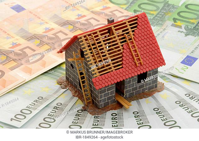 Model of a house under construction on banknotes, symbolic image for mortgage
