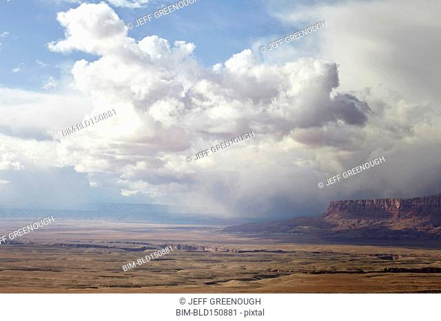 Puffy clouds rolling over rock formations in desert landscape, Page, Arizona, United States