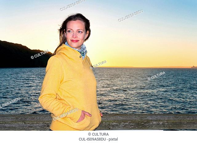 Portrait of mid adult woman, standing by sea, at sunset