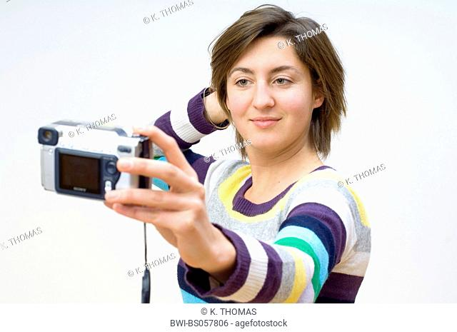 young woman with a digital camera, making a picture of herself