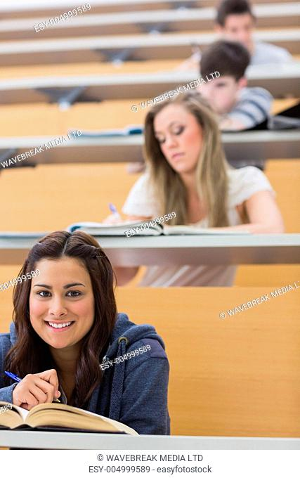 Student sitting reading a book while smiling in lecture hall
