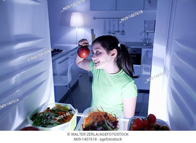 Girl takes an apple from the fridge