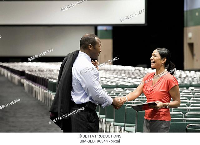 Black businesspeople greeting each other in conference center