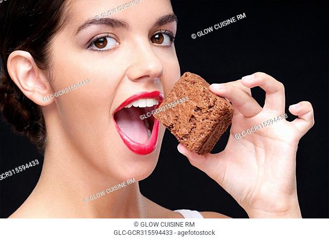 Close-up of a woman eating a brownie