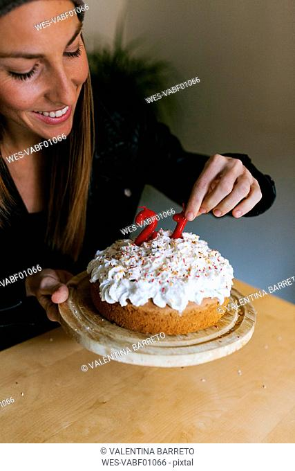 Young woman decorating birthday cake with red candles