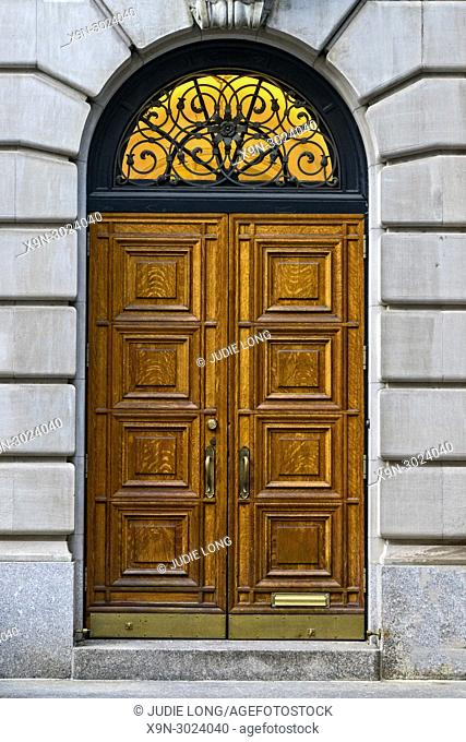 Elegant Carved Double Wooden Doors and Arched Ironwork Window, on an Elegant Townouse. Upper East Side, Manhattan, New York City