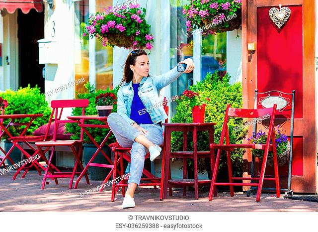 Young woman with her phone at outdoor cafe
