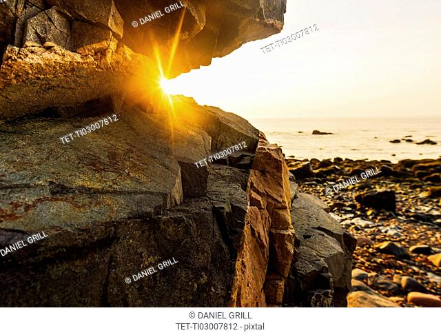 Rock formations on beach and sea at sunrise