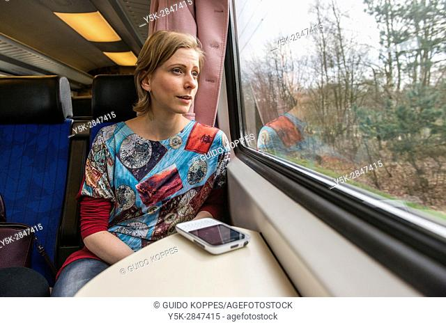 Tilburg, Netherlands. Young adult caucasian female commuting by intercity train to her assignmenet as a musical teacher