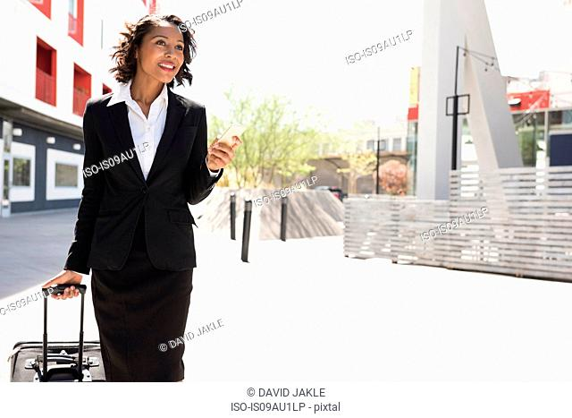 Young businesswoman, pulling suitcase, outdoors