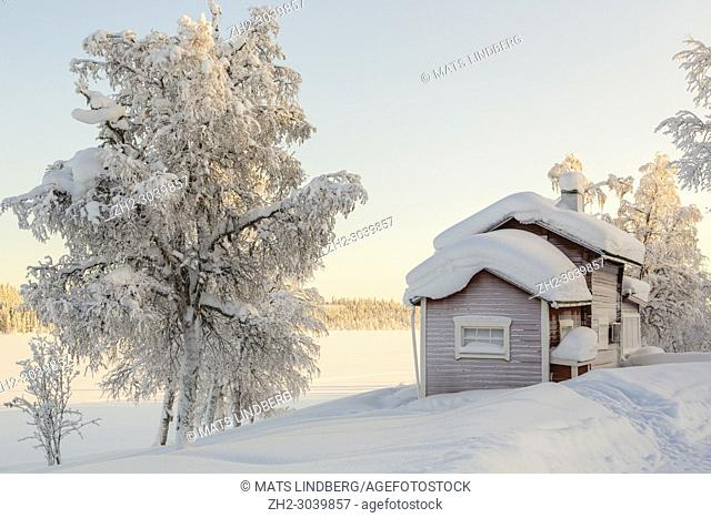 Winter landscape with abandoned cottage, clear skye and nice warm light, Gällivare county, Swedish Lapland, Sweden