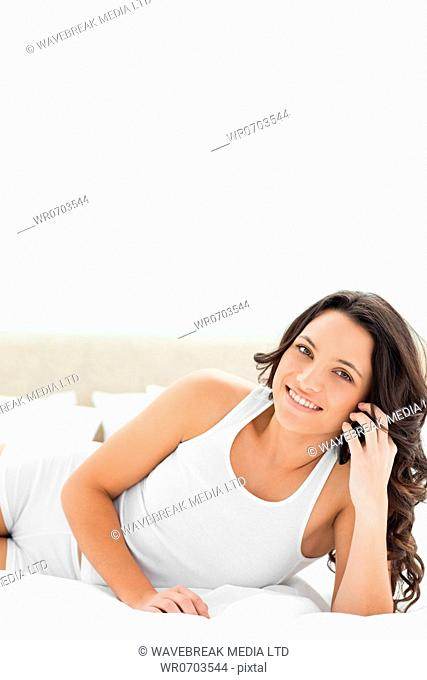 Close-up of a brunette smiling while phoning with a smartphone on her white bed