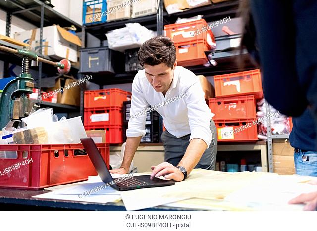 Man using laptop in demonstration in warehouse