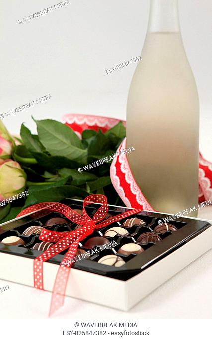 Bunch of roses, champagne bottle and assorted chocolate box