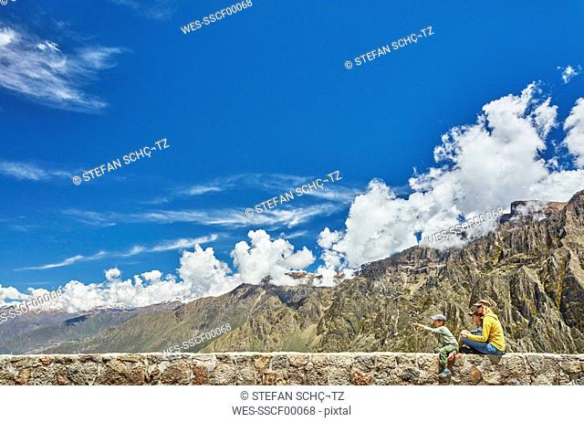 Peru, Chivay, Colca Canyon, woman sitting with sons on wall looking at canyon