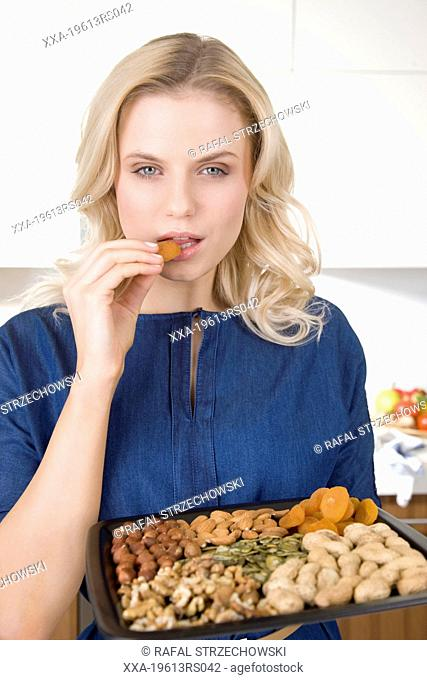 Woman eating nuts and dried fruits