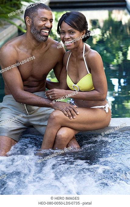 african american couple sharing a laugh by the pool
