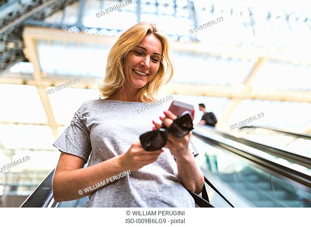 Mature woman moving down railway station escalator looking at smartphone