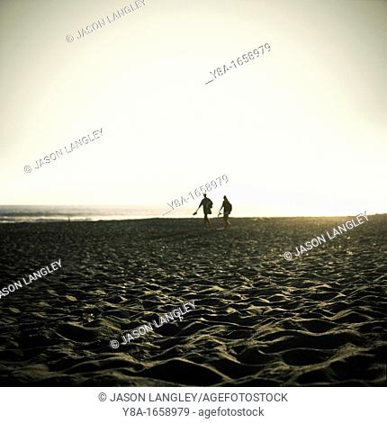 Two people silhouetted against the setting sun, Stinson Beach, California, United States