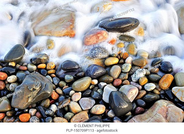 Colourful water smoothed pebbles in surf at shingle beach