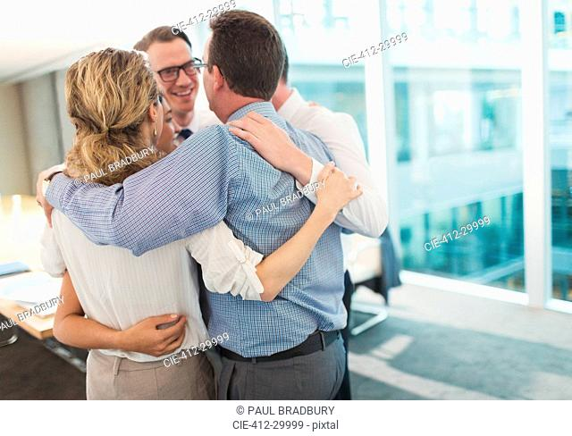 Smiling business people hugging in huddle in conference room