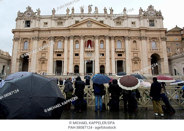 Journalists await the smoke signal from the chimney of the Sistine Chapel in the rain on St. Peter's Square in Vatican City, Vatican, 12 March 2013