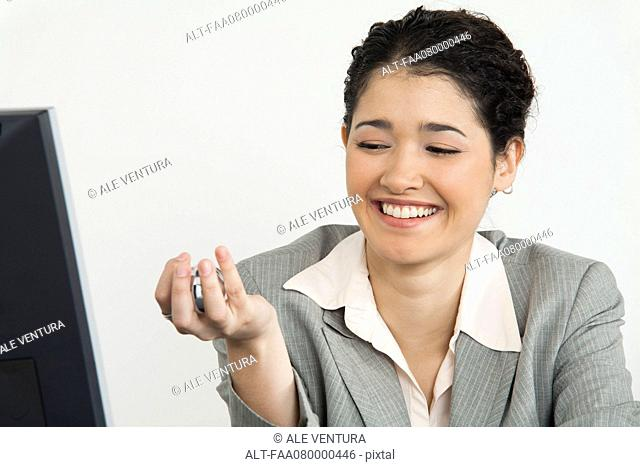 Young businesswoman holding yin yang balls, smiling