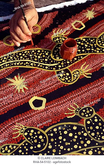 Artist of the Walpiri tribe using a stick to make dream paintings, in Australia, Pacific