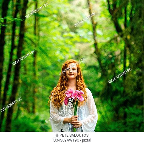 Young woman holding bunch of pink gerberas in forest