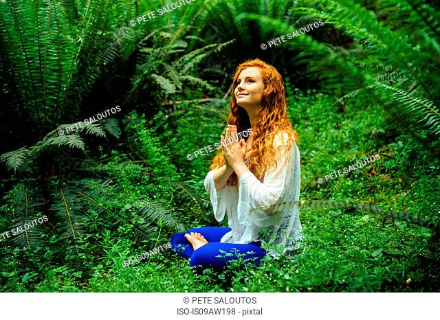 Young woman in forest practicing yoga in lotus position