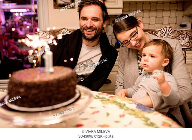 Couple and baby boy with first birthday cake