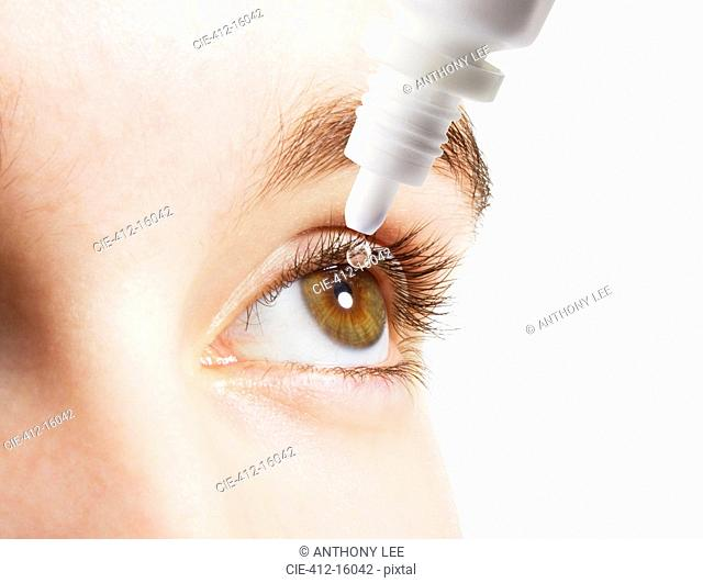 Extreme close up of woman inserting eye drops in eye