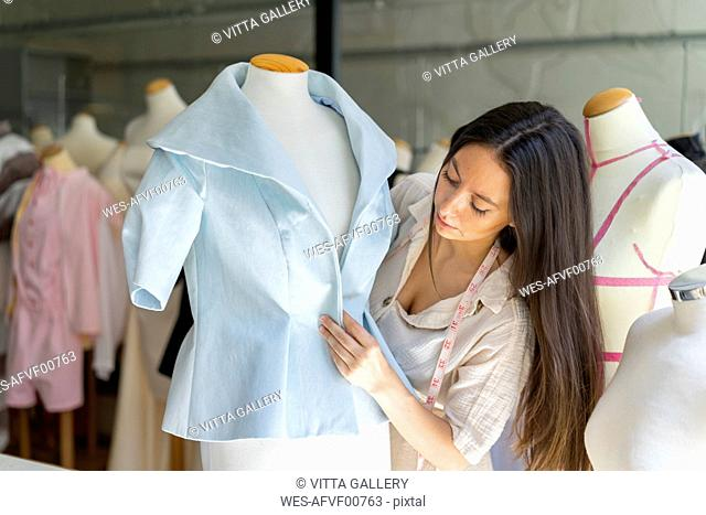 Young fashion designer fitting clothes on dressmaker's model