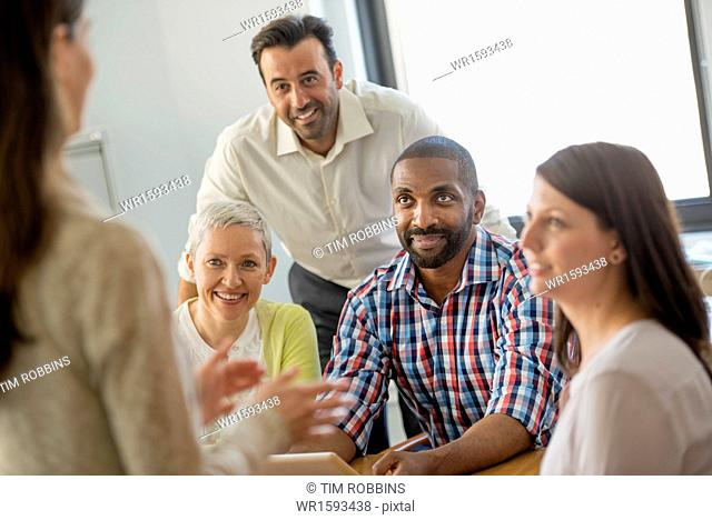 Five people in an office, two men and three women talking